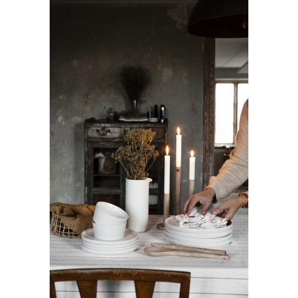 Frau mit ERNST Geschirr und Handtuch auf Tisch