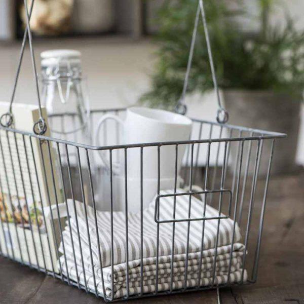Stahleinkaufskorb mit weißen Tassen, weißen Küchentücher, Glaskaraffe und Buch