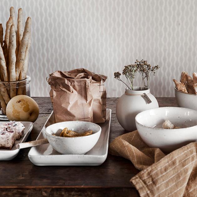 ERNST Produkte auf einem Tisch mit Broten und Blumen in Vasen