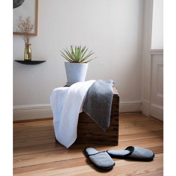 Weißes und graues Handtuch auf einer Holzkiste