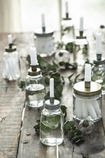 Kerzenhalter auf Glasvasen mit weißen Kerzen