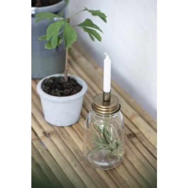 Kerzenhalter auf einer Glasvase und eine Pflanze in einem grauen Topf
